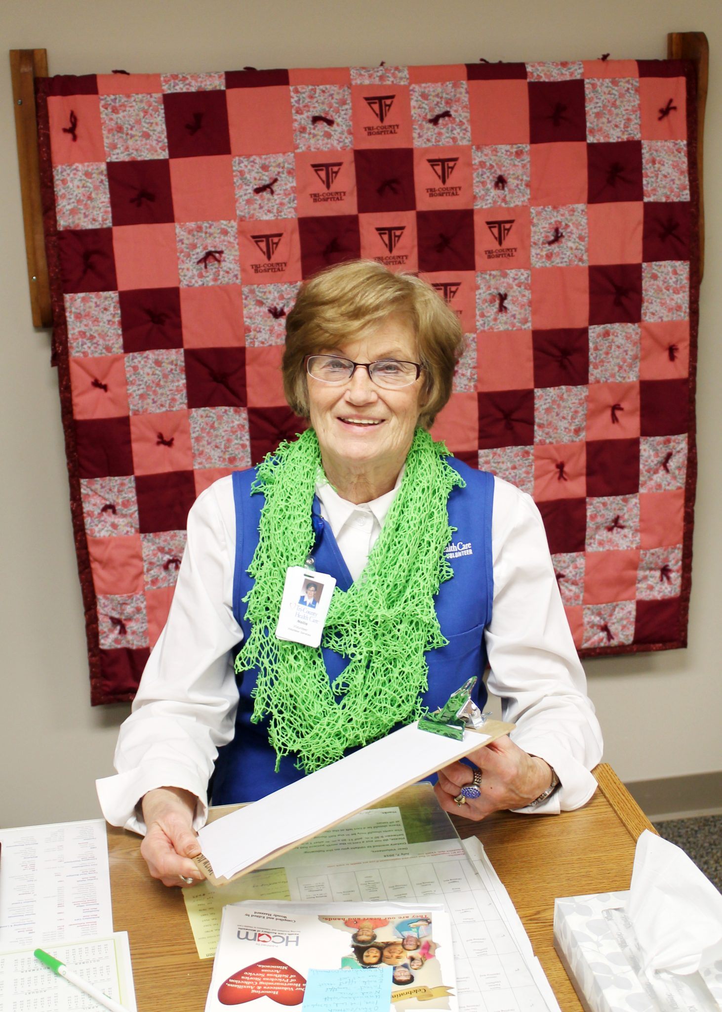 Nellie Welshed sitting at her desk in the surgical waiting room, in front of one of the quilts the auxiliary made & donated to TCHC.