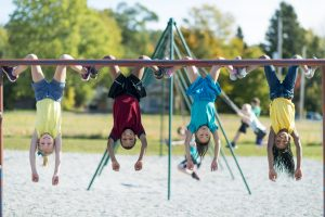 Kids playing outside on a jungle gym during recess.