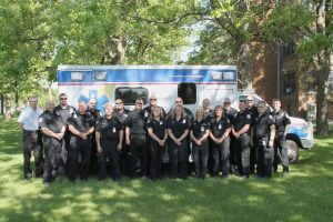photo of the TCHC EMS team standing in front of a TCHC ambulance