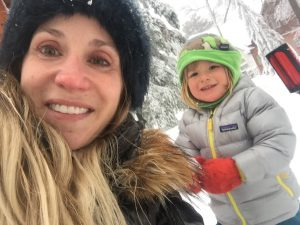 Dr. Arnhold playing in the snow with her son.