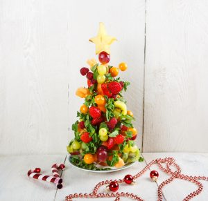 Fruit Christmas tree with different berries, fruits and mint.