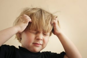 A four year old boy scratching his  itchy scalp from head lice