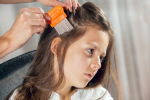 Mother using a comb in child's hair to look for head lice