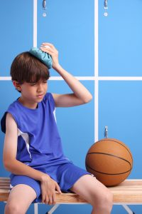 Young injured boy playing the sport of basketball holding an ice bag on his head.