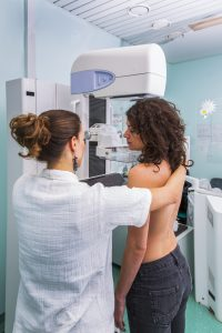 Nurse with a young woman having a mammogram.