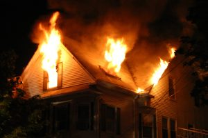 photo of a wood framed home with heavy fire showing on floor number 3