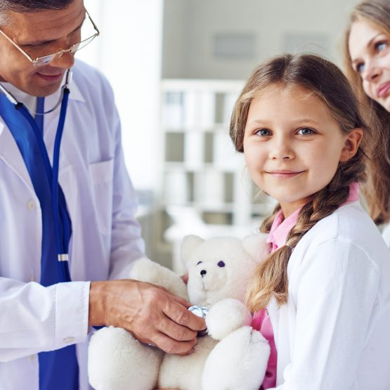 Little girl with teddy bear visiting doctor