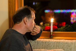 A Depressed adult male looks out a window past christmas decorations with christmas lights in the background.