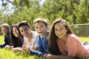 Diverse group of teenage friends hang out outside together at a local park or school campus.