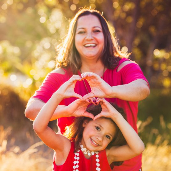 Mother and daughter showing love by making heart shape with hands.