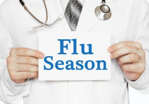 Doctor holding a card with Flu Season., medical concept
