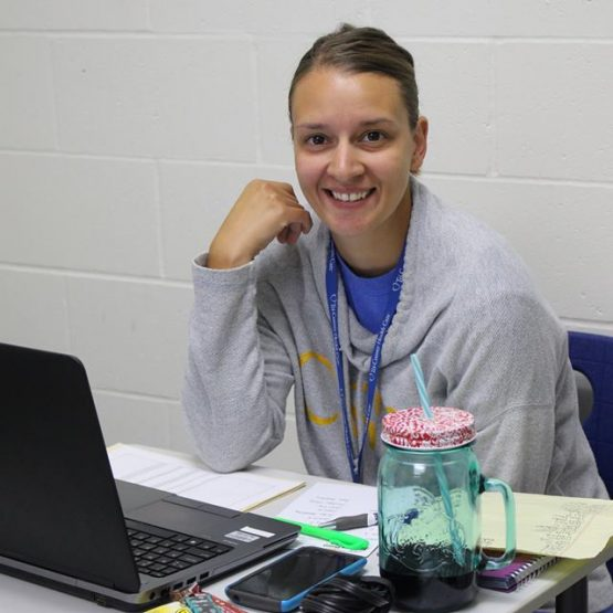 Athletic Trainer, Sarah Maninga, sits at her desk behind her computer and smiles for the camera.
