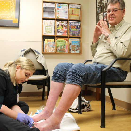 Photo of a patient having his feet treated by a nurse at a TCHC foot care clinic.