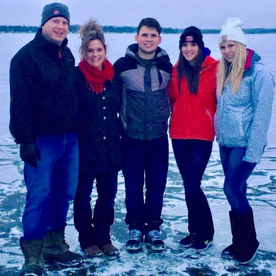 A photo of Thomas Williams, who was saved by the TCHC emergency department, with his family posing for a photo on the frozen lake.