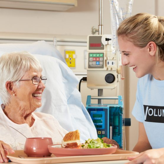 Teen Volunteer Serving Senior Female Patient A Meal