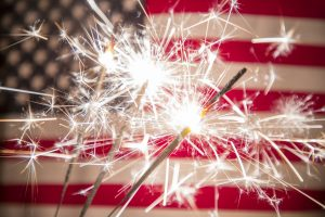 A photo of a USA stars and stripes flag with sparklers in the foreground representing the 4th of July.