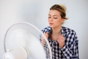 Girl with hot flashes has face cooling in front of a fan.