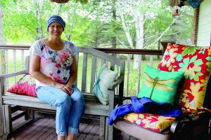 Breast cancer patient, Gretchen Noon sitting on her porch.