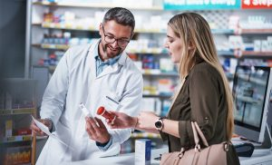 pharmacist shows woman prescription refill instructions
