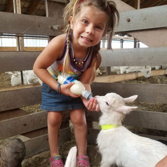 Savhannah feeding a baby goat on the farm.
