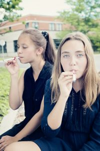 Two teenagers smoking e-cigarettes for the first time in a deserted school backyard. Both have long hair and are wearing dark dresses. The one in front is defiantly looking at the camera. School in the background, early fall or late spring time. Waist up shot vertical with copy space.