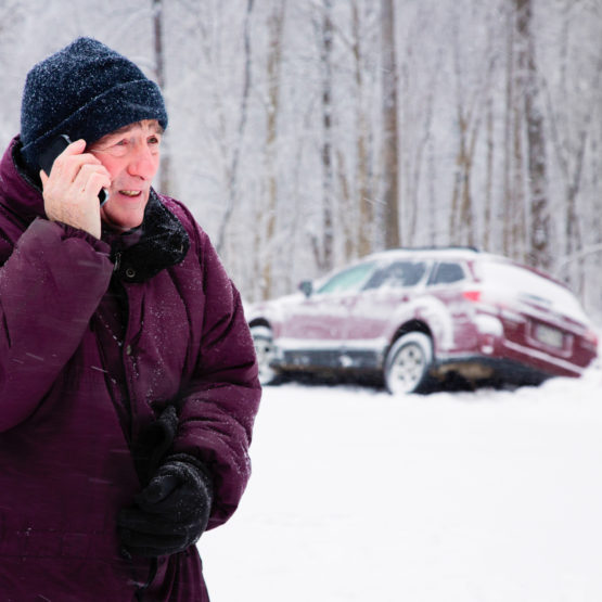 Senior man calling for help during a winter snow storm. His car lies in the ditch.