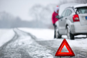 warning triangle with winter car breakdown in background.