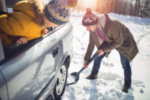 Photo of Man cleaning snow in the winter near the car with shovel in nature.