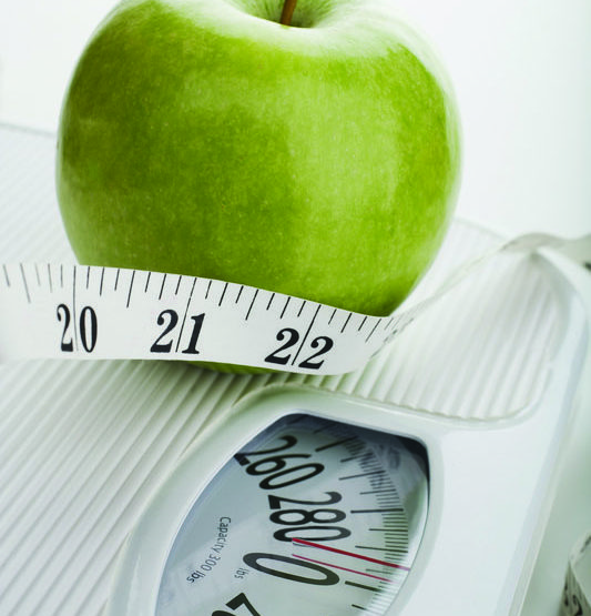 A green apple, scale and tape measure highlighting the importance of good nutrition.
