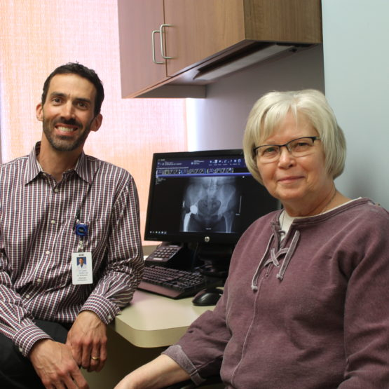 Arthritis patient, Jean Wallgren, smiling and sitting next to orthopedic surgeon Ben Robertson.
