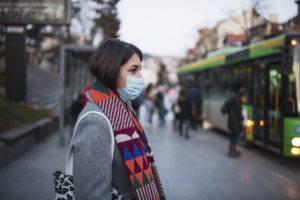 Side view of young woman with protective coronavirus face mask in town, she standing in front at the bus stop and waiting for her transport after work.