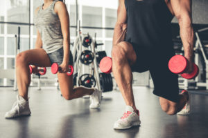 Attractive sports people are strength training with dumbbells in gym
