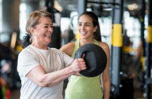 Adult wstrength training at the gym with a personal trainer and looking very happy - healthy lifestyle concepts