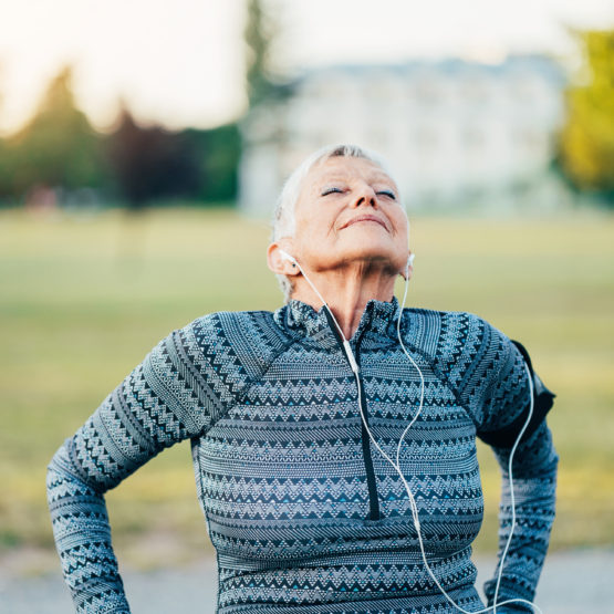 Senior sportswoman breathing in fresh air with arm band and headphones outdoors in the park