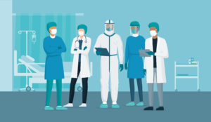 Professional doctors and nurses posing together in a hospital ward and wearing protective suits, coronavirus outbreak emergency concept
