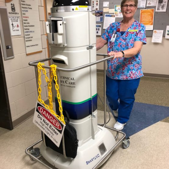 Ultraviolet cleaning machine used to disinfect and kill the Coronavirus. Housekeeping employee stands behind and pushes machine along.