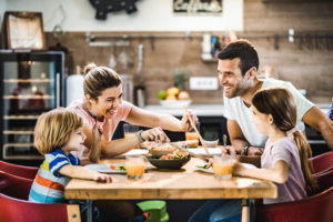 Happy family talking while having dinner in dining room.
