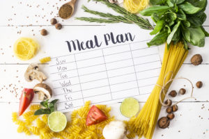 A meal plan for a pandemic week on a white table among products for cooking - pastas, basil, vegetables, lime, seeds, nuts and spices.