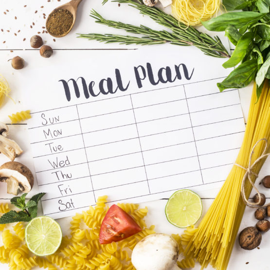 A meal plan for a week on a white table among products for cooking - pastas, basil, vegetables, lime, seeds, nuts and spices.