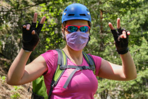 Woman alpinist wearing a medical mask and helmet, shows a victory sign with both hands. Concept of Coronavirus (Covid-19) restrictions being eased and people returning to outdoor activities.