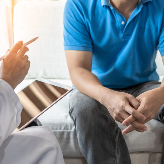 Men's health with male patient having consultation with doctor or psychiatrist working on diagnostic examination in medical clinic or hospital