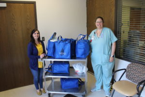 Breast Milk Donor Stacy Kinnen stands next to Sarah Reidel, OB supervisor along with a cart full of breast milk she donated to babies in need.